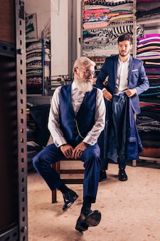 Male fashion designer holding coat with his customer sitting on chair in the shop
