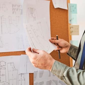 新しい服のラインの計画と紙を保持している男性のファッションデザイナー