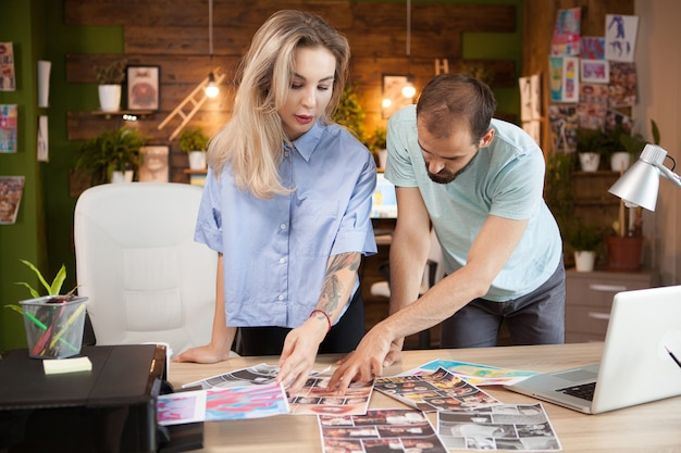 사무실에서 창의적인 아이디어를 가리키는 남성 패션 디자이너. 여성 재단사.