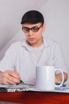 彼のアトリエでスケッチに取り組んでいる男性のファッションデザイナー。
