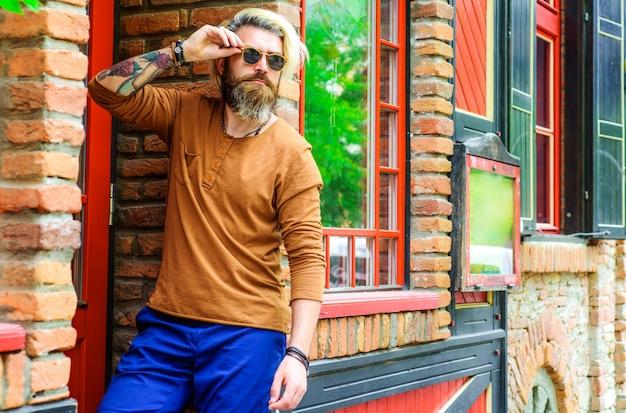 男性のファッション。サングラスのスタイリッシュなハンサムな男。メガネのひげを生やしたヒップスター。