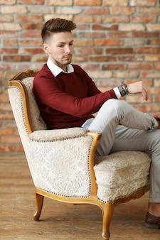 Moda maschile sul pavimento di legno, giovane in posa