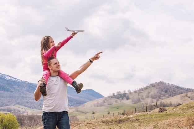 남성 아버지와 손에 흰색 장난감 비행기와 작은 딸