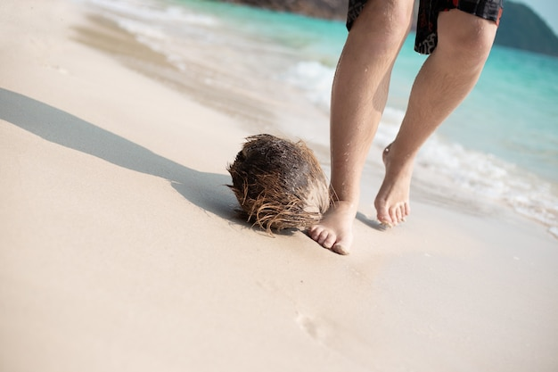 Male feet barefoot on white sand by the sea, next to a coconut