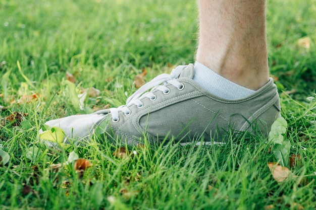 Male feet in gray gumshoes on grass