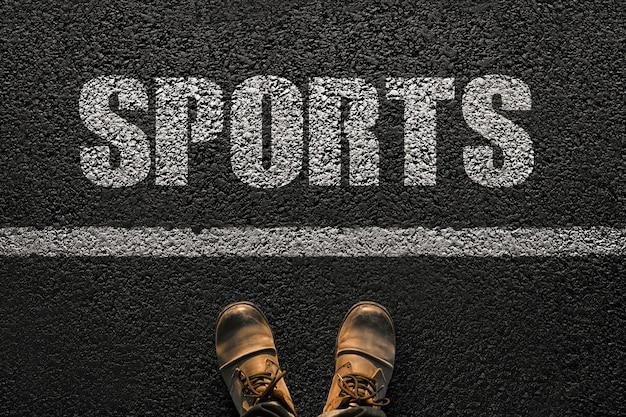 靴を履いた男性の足は、テキストスポーツ、上面図でアスファルトの上に立っています。健康的なライフスタイルとスポーツのコンセプト。健康クリエイティブへの一歩