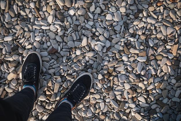 Мужские ноги в кроссовках стоят на дороге из камня