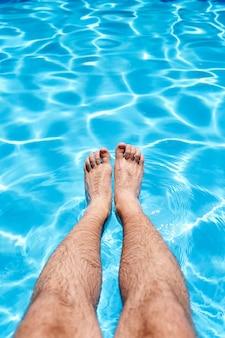 태양 근접 촬영 아래 수영장에서 푸른 물 위에 남성 발
