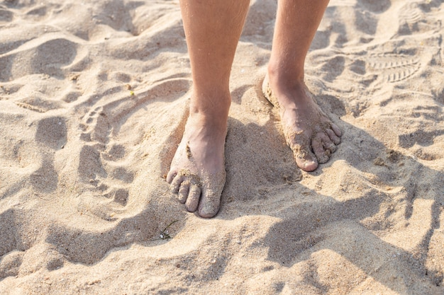 Male feet in the sand. walk along the sandy sea beach on a summer day. travel and tourism.