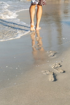 Male feet on the shore of a sandy beach on a sunny day. young man walks along the edge of the water leaving footprints. space for text. tourism and rest.