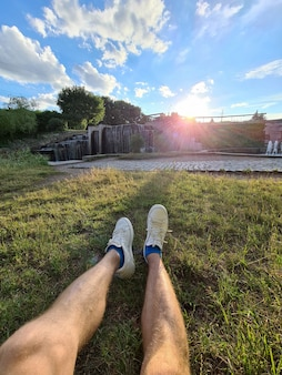 Male feet in white sneakers lying on green grass against background of waterfall closeup