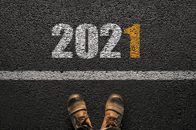 アスファルトにブーツを履いた男性の足。白い線と2021年の新年の数字。成功したスタートのコンセプト。未来へのステップ
