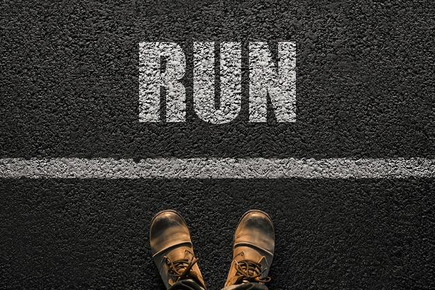 ブーツを履いた男性の足が白い線の近くのアスファルトの上に立っており、言葉が走り、健康的な生活の選択です。コンセプトの健康と成功。