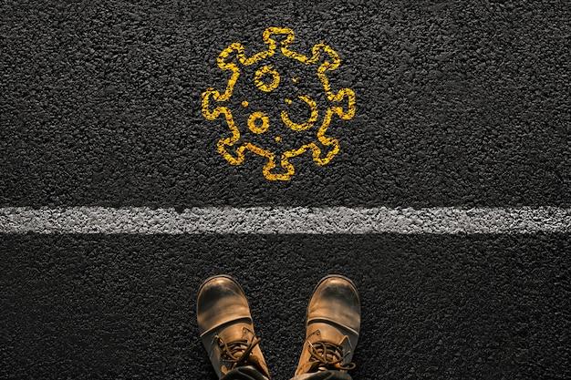 靴を履いた男性の足は、黄色のペンキからの線とウイルスでアスファルトの上に立っています。旅行とcovidのコンセプト。感染症とパンデミック