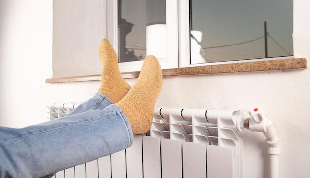Мужские ножки в носках на радиаторе. отопительный сезон.