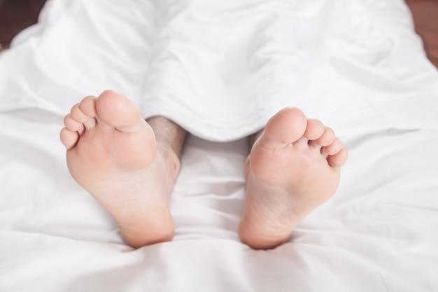 Мужские ноги на кровати утром