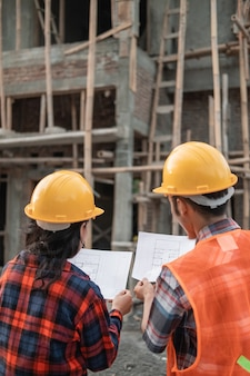 Male and female asian contractors standing wearing safety helmets holding the site plan building