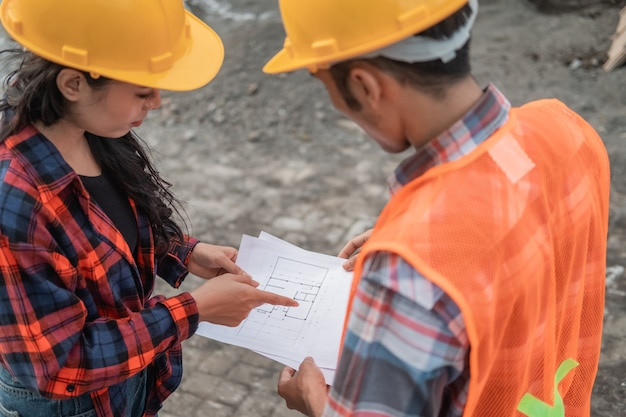 Male and female asian contractors wearing safety helmets holding the site plan building during building construction