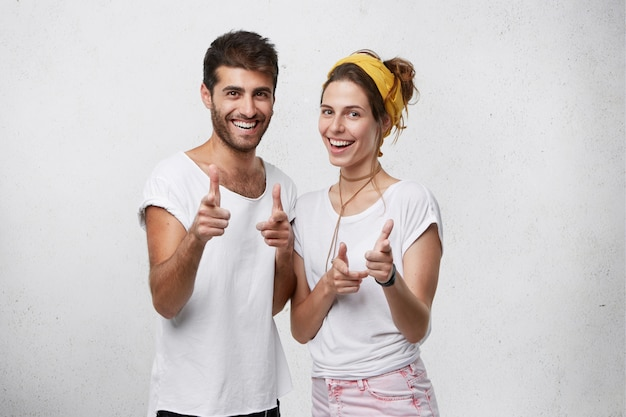Male and female best friends with positive expression looking with pleasant smiles pointing at you with fingers having fun and good rest posing