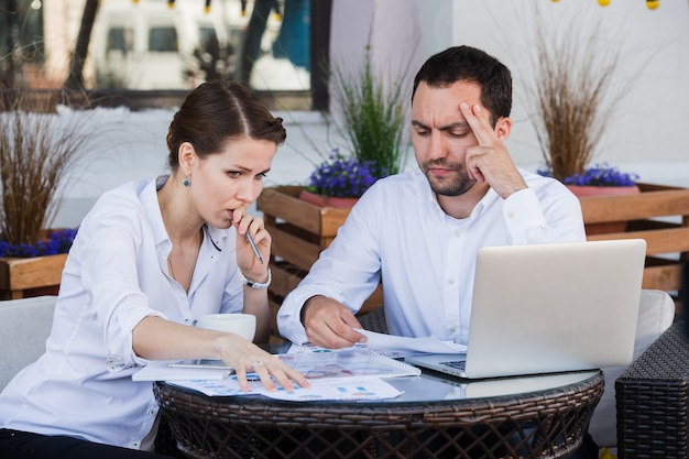 Male and female business colleagues working together on a hard problem at outdoors cafe. they have strained expression on their faces
