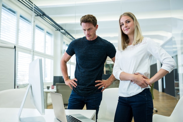 Male and female business executives standing with hands on hips
