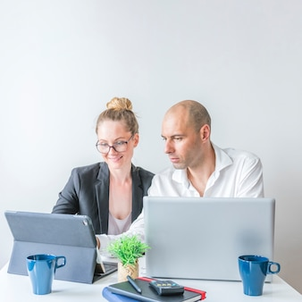 Male and female businesspeople using laptop at workplace