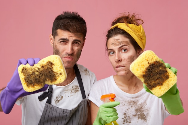Male and female in casual clothes having dirty faces demonstrating dirty sponges