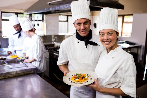 Male and female chefs holding plate of prepared pasta in kitchen