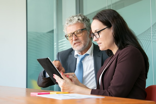 Male and female colleagues using tablet together, looking and pointing at gadget screen while sitting at table in office.