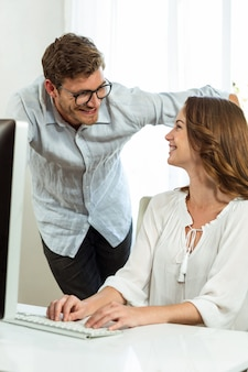 Male and female collegues smiling while using computer at office desk