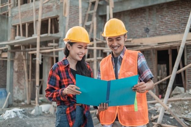 Male and female contractors standing holding a sketch book