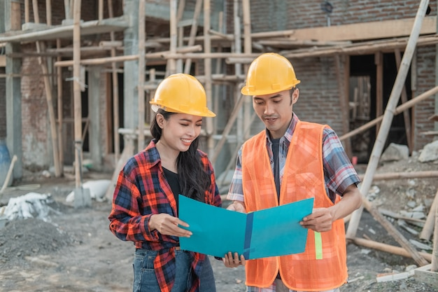 Male and female contractors standing  wearing safety helmets against the background of the unfinished building