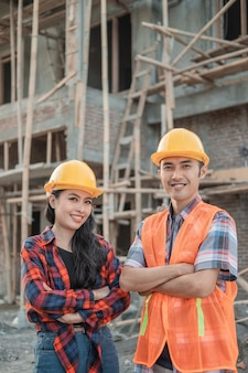 Male and female contractors standing with crossed hands smiling at the camera wearing safety helmets against the background of the unfinished building