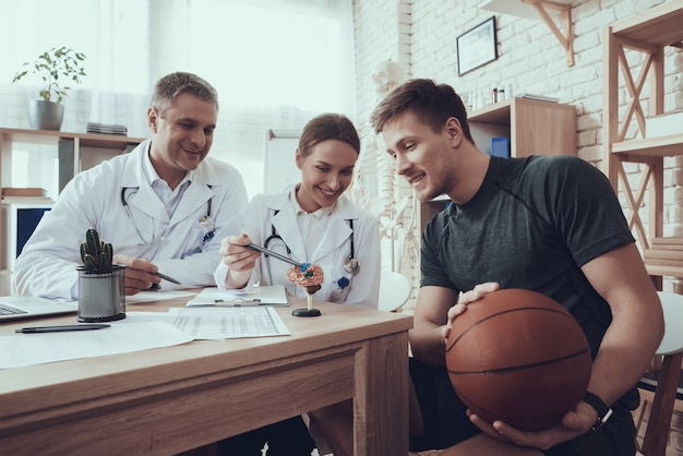 Male and female doctors in clinic with basketball player.