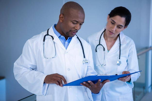 Male and female doctors having over clipboard in corridor