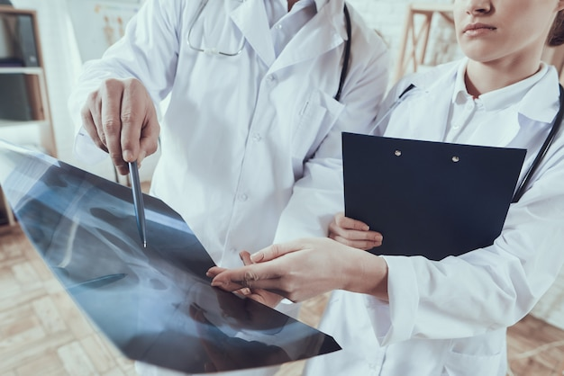 Male and female doctors in white gowns with stethoscopes