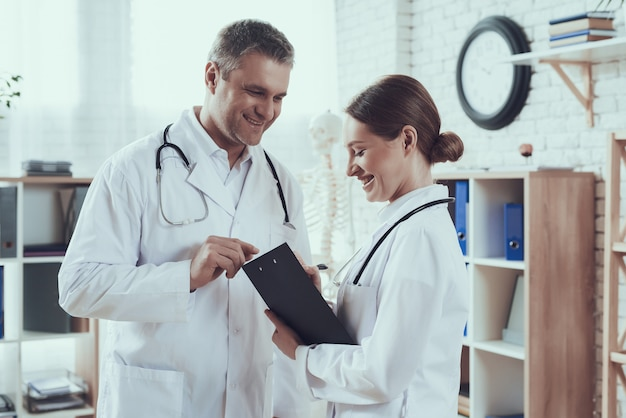 Male and female doctors with stethoscopes in office