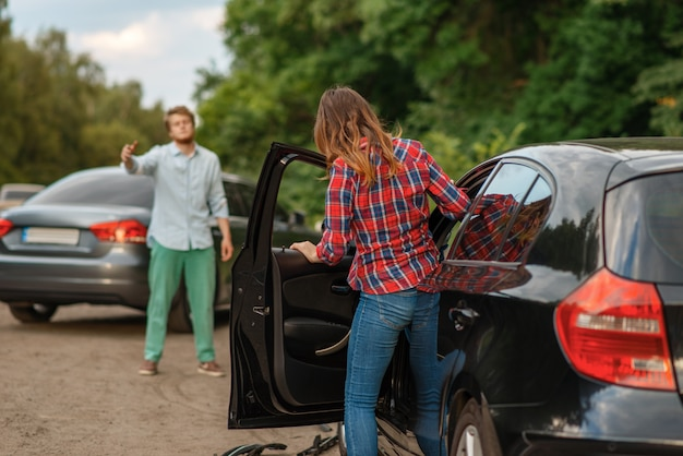 Male and female drivers after car accident on road. automobile crash. broken automobile or damaged vehicle, auto collision on highway