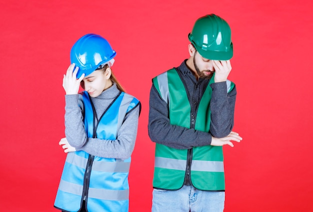Male and female engineers wearing helmet and gear look tired and sleepy.