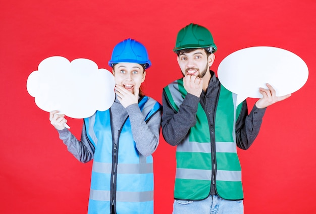 Male and female engineers with helmet holding a cloud and ovale shape info board and look surprized and confused.
