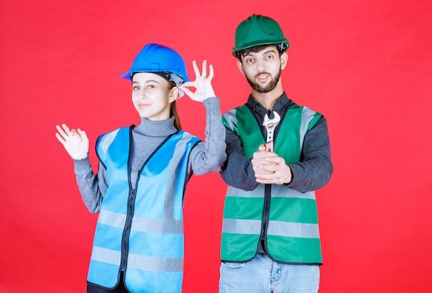 Ingegneri maschii e femminili con il casco che tiene una chiave metallica e che mostra il segno positivo della mano.