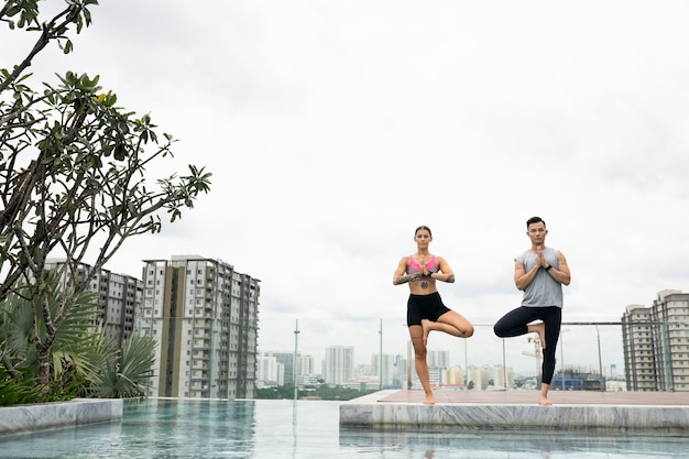Amici maschii e femminili che praticano yoga insieme