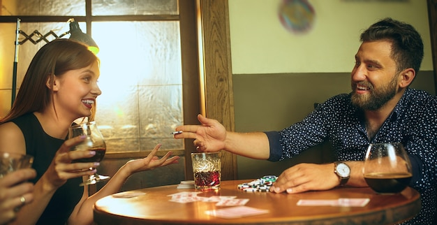 Male and female friends sitting at wooden table. men and women playing card game. hands with alcohol close-up.