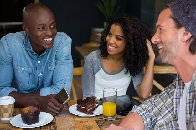 Male and female friends talking at table in coffee house