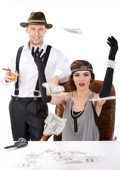 Male and female gangsters sitting at a table counting money.