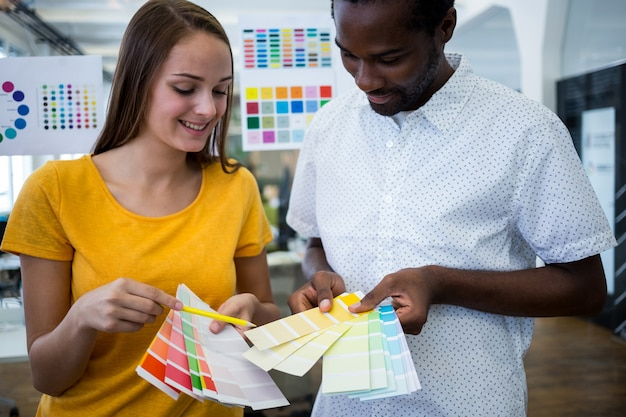 Male and female graphic designers choosing color from the sampler