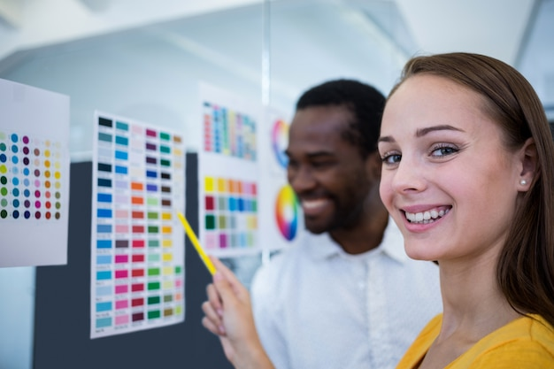 Male and female graphic designers interacting over color chart