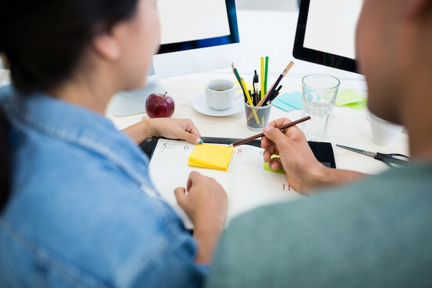 Male and female graphic designers writing on diary