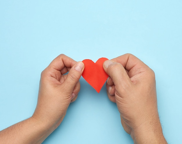 Male and female hand holding red paper heart
