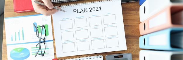 Male and female hands holding ballpoint pen with documents with plan for 2021 at table in office